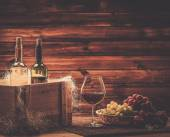 Bottles of red and white wine, glass and grape on a wooden interior  — Stock Photo