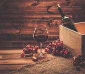 Bottle, glass and red grape on a wooden table  — Stockfoto