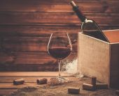 Bottle and glass of red wine on a wooden table  — Stockfoto