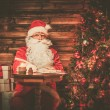 Santa Claus in wooden home interior sitting behind table and writing letters with quill pen — Stock Photo #53348213