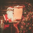 Santa Claus in wooden home interior holding blank wish list scroll — Stock Photo #53348221