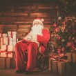 Santa Claus sitting on rocking chair in wooden home interior with gift boxes around him — Stock Photo #53348243