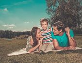 Young family with their child lying on a blanket outdoors — Stock Photo