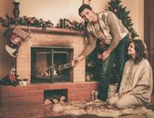 Couple putting log into  fireplace in Christmas decorated house interior  — ストック写真
