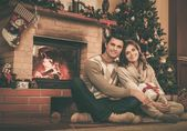Couple near fireplace in Christmas decorated house interior  — Stock Photo