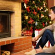 Man with cup of hot drink near fireplace in Christmas decorated house — Stock Photo #54788125