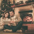 Couple near fireplace in Christmas decorated house interior  — Stock Photo #54788175