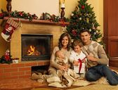 Family near fireplace in Christmas decorated house interior with gift box — Stock Photo