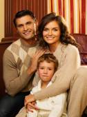Family in warm cashmere clothes in home interior  — Stock Photo