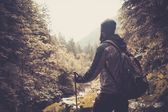 Man with hiking equipment walking in mountain forest — Foto de Stock