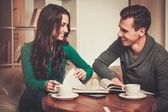 Couple with coffee and book discussing something in cafe  — Stock Photo