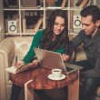 Young couple with laptop and coffee behind table — Stock Photo #55350013