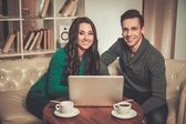 Young couple with laptop and coffee behind table — Stock Photo