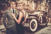 Beautiful retro couple against vintage car — Stock Photo