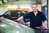 Cheerful worker wiping car on a car wash — Stock Photo