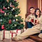 Happy family near Christmas tree in house interior — Stock Photo #56717923