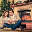 Couple near fireplace in Christmas decorated house interior  — Stock Photo #56717983