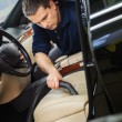 Worker on a car wash cleaning car interior with vacuum cleaner  — Stock Photo #56718003