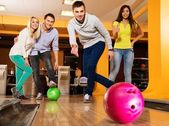 Group of four young smiling people playing bowling  — Foto de Stock