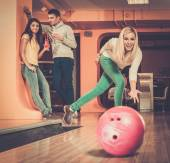 Blond smiling girl throwing ball in a bowling club   — Stock Photo
