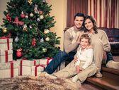 Happy family near Christmas tree in house interior  — Foto de Stock