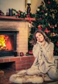 Young woman near fireplace in Christmas decorated house interior  — Foto de Stock