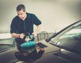Man on a car wash polishing car with a polish machine  — Stock Photo