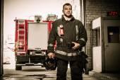 Firefighter against truck in firefighting depot  — Stock Photo