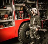 Firefighter in storage room with fire hoses — Stock Photo