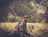 Man with hiking equipment walking in mountain forest — Stock Photo