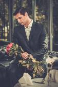 Handsome man with bunch of red roses waiting his lady in restaurant  — Foto de Stock
