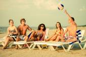 Group of multi ethnic friends with drinks relaxing on a beach — Stock Photo