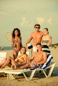 Group of multi ethnic friends with ball and racket on a beach  — Stock Photo