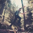 Man hiker jumping across stream in mountain forest — Stock Photo #57139043