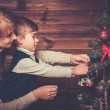 Happy mother and her lIttle boy decorating christmas tree in wooden house interior  — Stock Photo #57139213