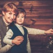 Happy mother and her lIttle boy decorating christmas tree in wooden house interior  — Stock Photo #57139217