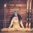 Happy woman with skis and ski boots sitting near wooden wall in snowflakes — Stock Photo #57139679