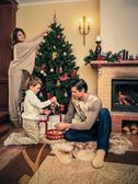 Happy family decorating Christmas tree — Stock Photo
