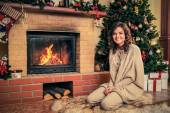 Young woman near fireplace in Christmas decorated house interior — Stock Photo