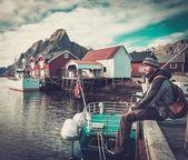 Man traveller sitting on a pier in Reine village, Norway  — Stock Photo