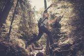 Man hiker jumping across stream in mountain forest — Stock Photo