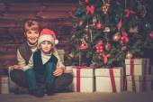 Mother and lIttle boy with gift box under christmas tree in wooden house interior  — Stock Photo