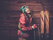 Smiling woman with skis and poles standing against wooden house wall  — Stock Photo