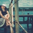 Beautiful woman wearing hat and white scarf sitting on old wooden pier — Stock Photo #57718177