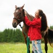 Beautiful smiling girl with her brown horse outdoors — Stock Photo #57718279