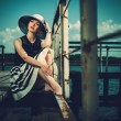 Beautiful woman wearing hat and white scarf sitting on old wooden pier — Stock Photo #58244869