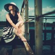 Beautiful woman wearing hat and white scarf sitting on old wooden pier — Stock Photo #58244921