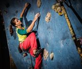 Young woman practicing rock-climbing on a rock wall indoors — Stock Photo