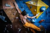 Muscular man practicing rock-climbing on a rock wall indoors  — Stock Photo