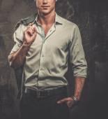 Handsome man in shirt against grunge wall holding jacket over shoulder — Stock Photo